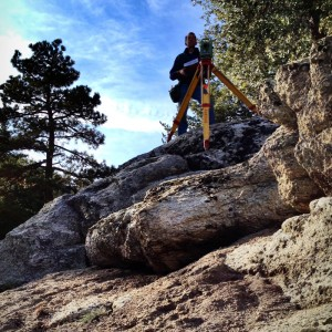 Surveying on a gravel covered boulder in Pine Cove
